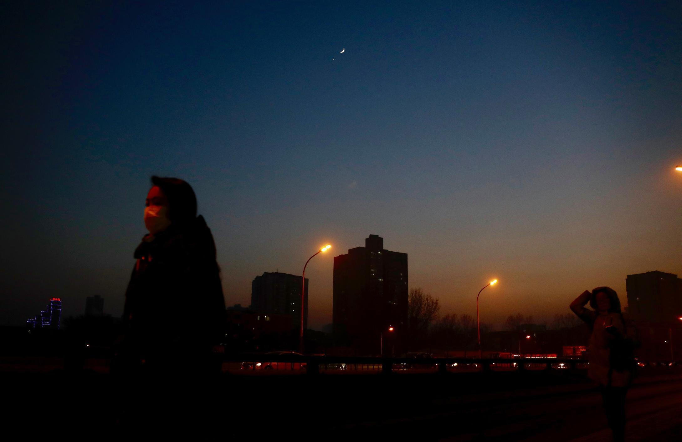 A star is twinkling above a pedestrian wearing a mask silhouetted against the city skyline shrouded in heavy smog in Beijing Monday, Jan. 2, 2017. Beijing and other cities across northern and central China were shrouded in thick smog Monday, Jan. 2, 2017, prompting authorities to delay dozens of flights and close highways. (AP Photo/Andy Wong)