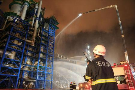 Firefighters spray water onto a fire at state oil major PetroChina's plant in Dalian, Liaoning province, China August 17, 2017. REUTERS/Stringer