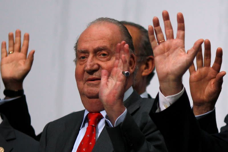 Spanish King Juan Carlos waves during a group photo with Ibero-American leaders during the Ibero-American Summit in Cadiz