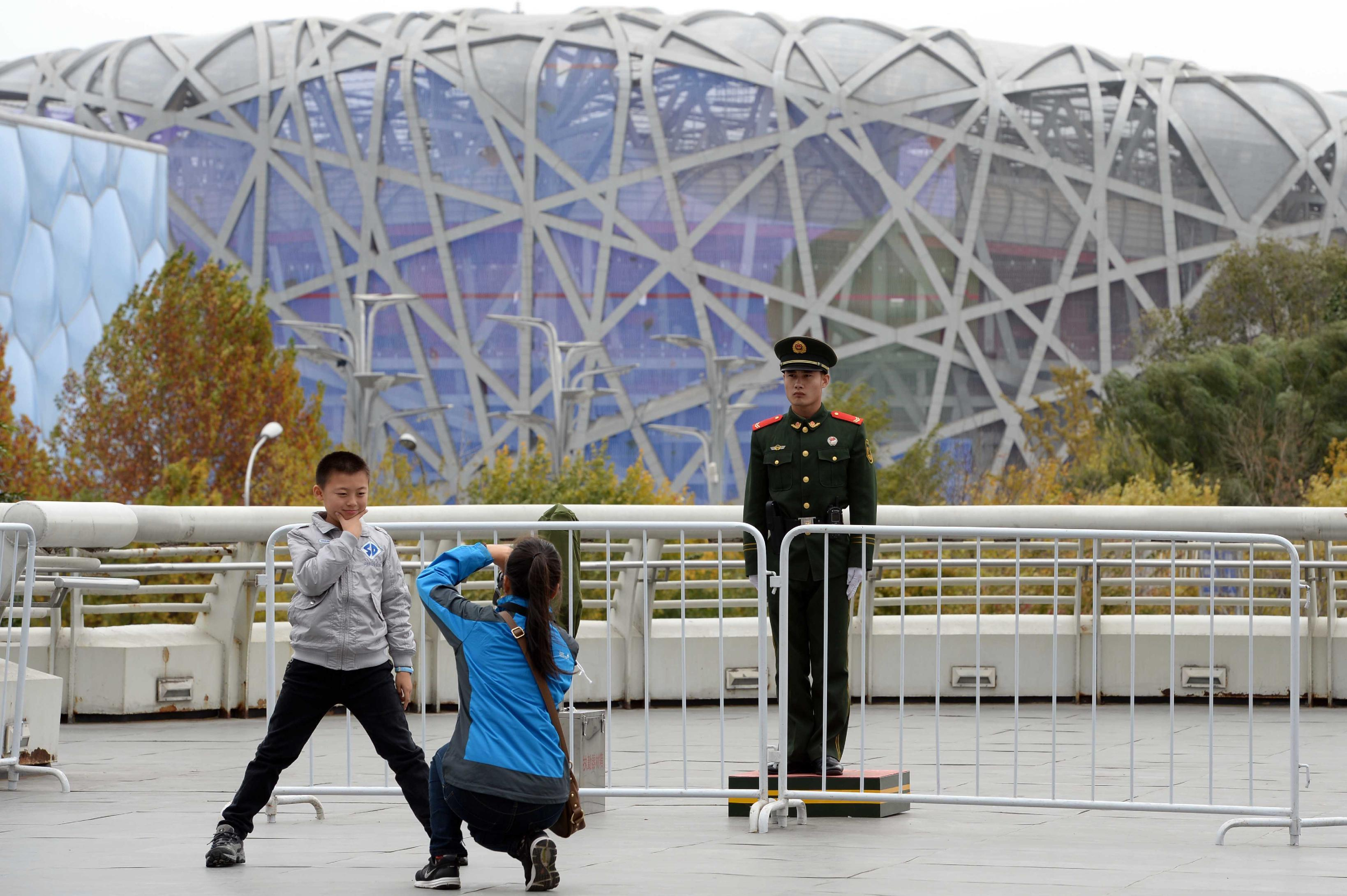 A boy (L) poses for a photo outside the China National Convention Center, one of the main venues of the annual APEC summit in Beijing (AFP Photo/)