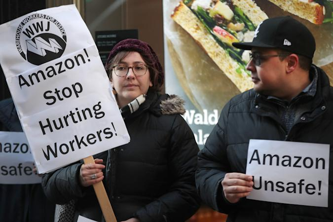 """CHICAGO, ILLINOIS - DECEMBER 10: Former injured Amazon employees join labor organizers and community activists to demonstrate and hold a press conference outside of an Amazon Go store in the loop to express concerns about what they claim is the company's """"alarming injury rate"""" among warehouse workers on December 10, 2019 in Chicago, Illinois. According to the community group Warehouse Workers for Justice, some Amazon warehouse facilities have injury rates more than twice the industry average, with peak rates occurring during the holiday season.   (Photo by Scott Olson/Getty Images)"""
