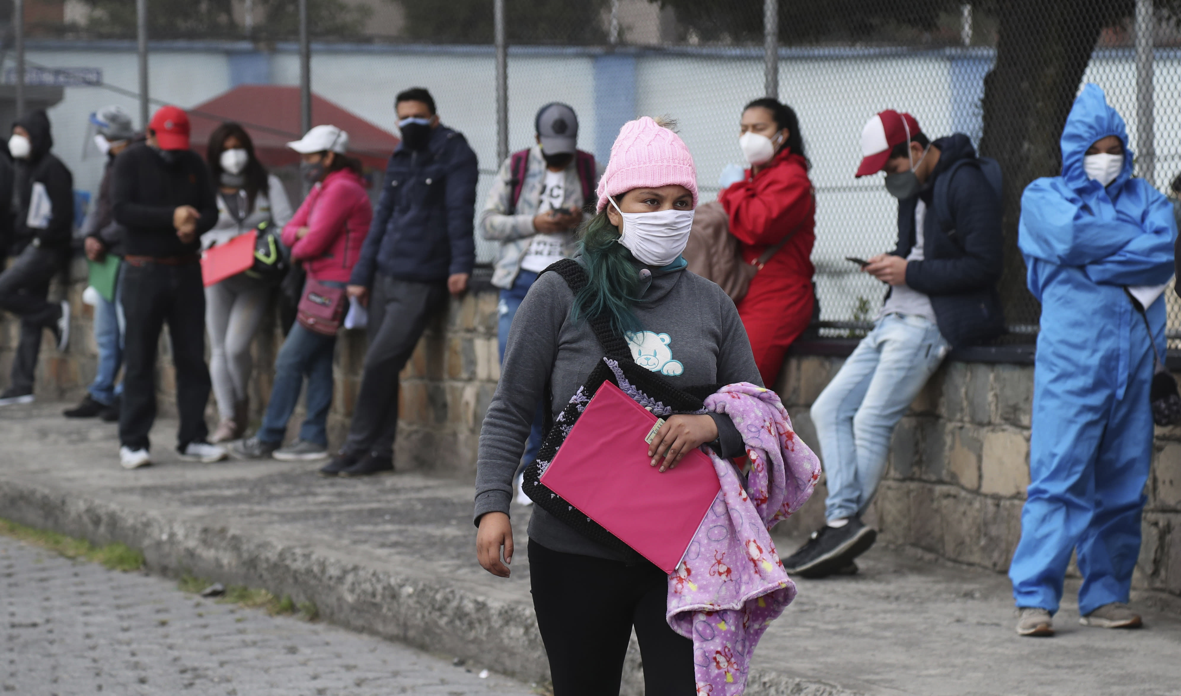 People wait in line to get COVID-19 tests, outside a health clinic in Quito, Ecuador, Wednesday, July 29, 2020. The Ecuadorian capital has experienced a surge in COVID-19 cases since the government started to reopen the economy last month. (AP Photo/Dolores Ochoa)
