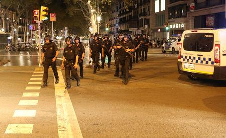 Armed Catalonian Mosses de Escuadra officers leave the area where a van crashed into pedestrians at Las Ramblas in Barcelona