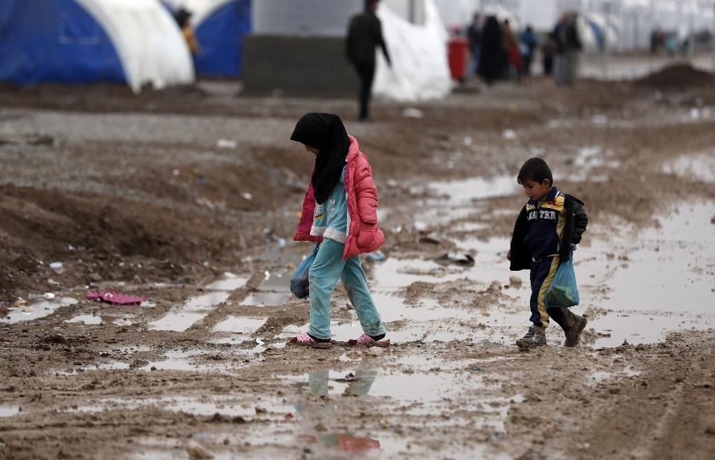 Iraqi children walk in the mud following heavy rain at the Khazir camp for displaced people, between Arbil and Mosul, on December 1, 2016 (AFP Photo/THOMAS COEX)