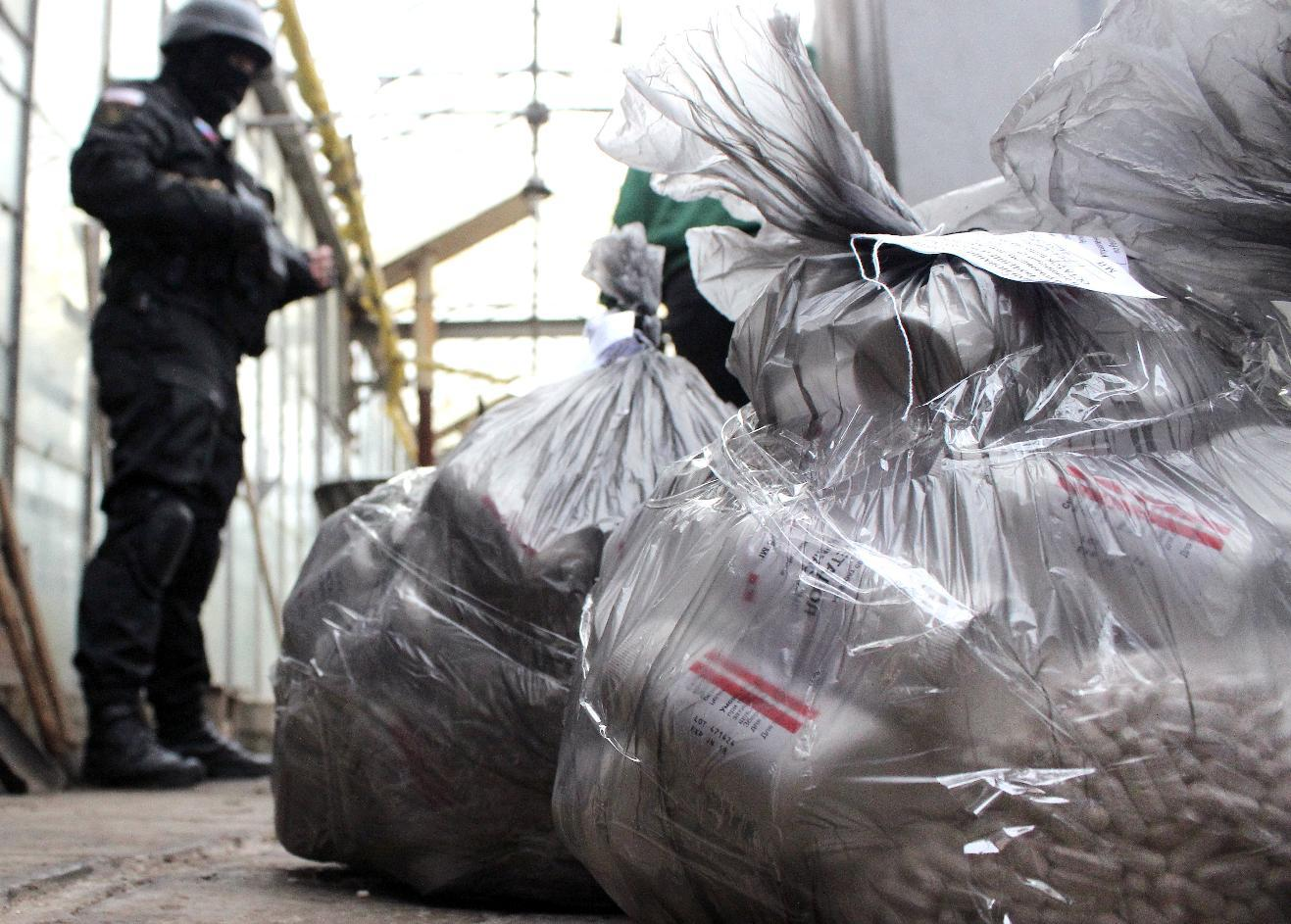 A Russian Federal Drug Control Service officer guards bags of Methadone before burning them during an operation in Simferopol on December 23, 2014 (AFP Photo/Yuri Lashov)