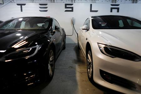 FILE PHOTO:Two Tesla Model 3 vehicles are shown charging in an underground parking lot next to a Tesla store in San Diego, California, U.S., May 30, 2018. REUTERS/Mike Blake/File Photo