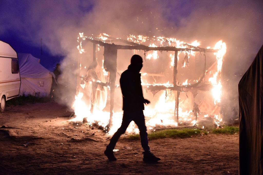"""A migrant walks past a shack that was set on fire during the demolition of the """"Jungle"""" camp in Calais, northern France, on October 25, 2016 (AFP Photo/Philippe Huguen)"""