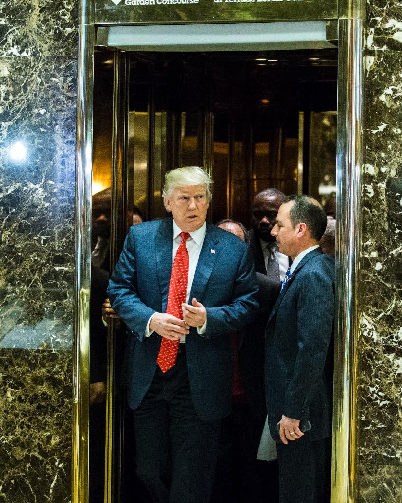 Donald Trump (left) exits the golden elevators to speak with media at Trump Tower on December 6, 2016 in New York (AFP Photo/Eduardo Munoz Alvarez)