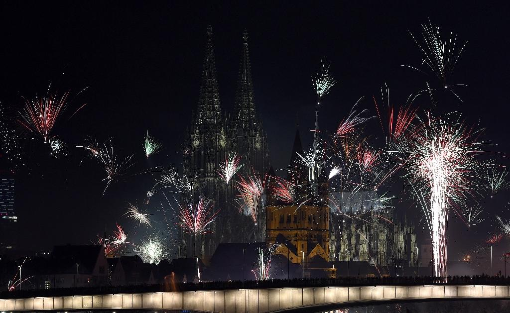Fireworks explode over the river Rhine in front of Cologne Cathedral during New Year's celebrations on January 1, 2016 (AFP Photo/Patrik Stollarz)