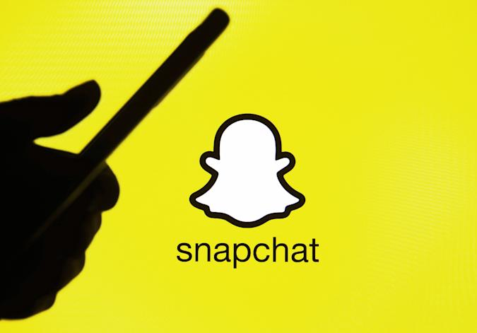 This illustration picture taken on 15 January 2021 shows the Snapchat logo in front of the silhouette of a hand holding a smartphone (Photo illustration by STR/NurPhoto via Getty Images)