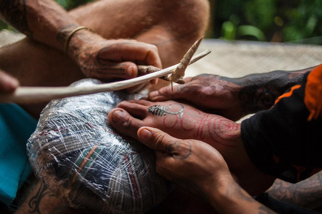 "A tattoo artist uses the traditional ""hand tapping"" method during a tattoo festival in the village of Maguwoharjo located in Yogyakarta (AFP Photo/Suryo Wibowo)"
