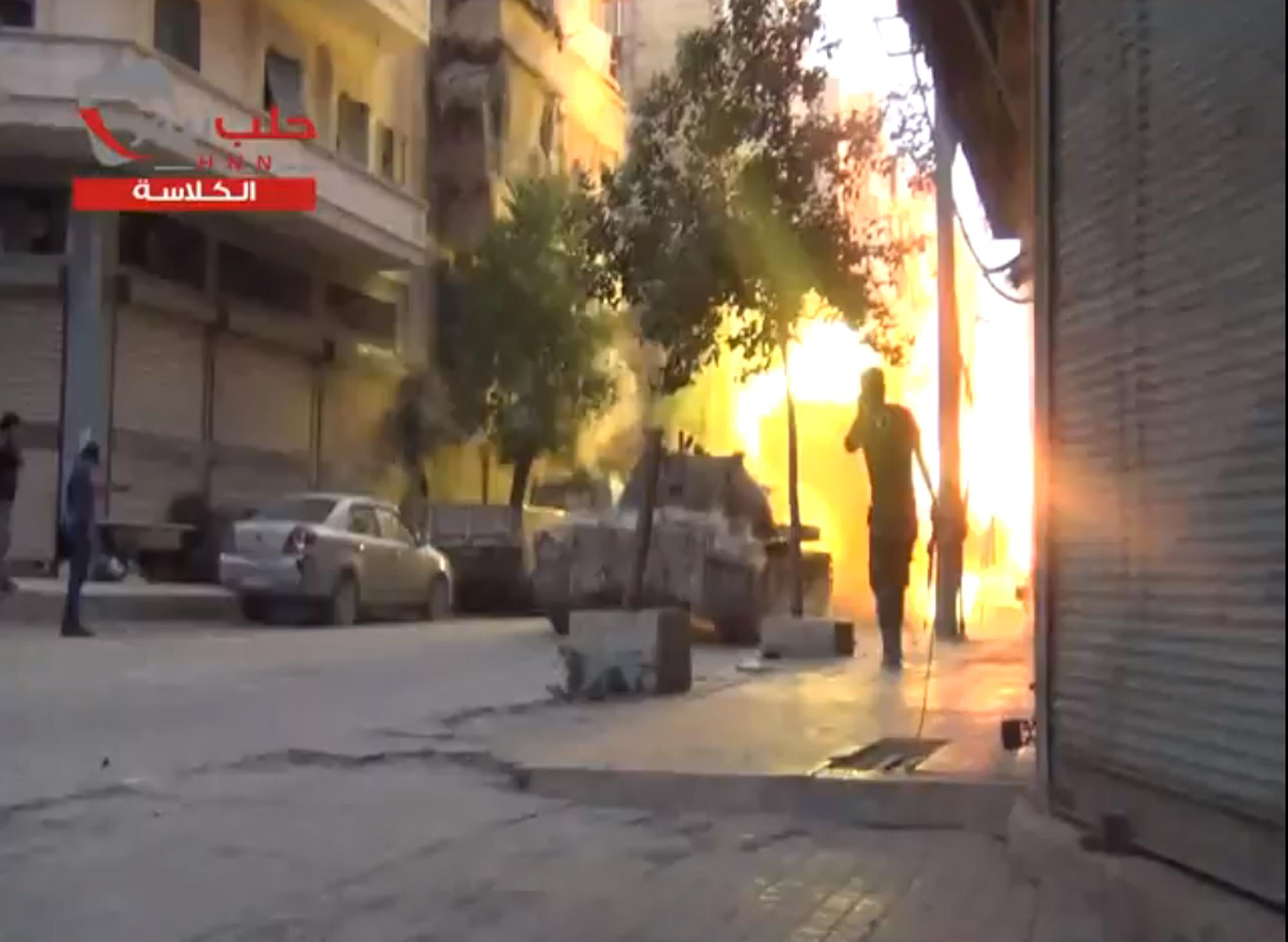 """In this image taken from video obtained from the Shaam News Network, which has been authenticated based on its contents and other AP reporting, fighters from the Free Syrian Army targets one of the bastions of the regime's forces with tank fire, Monday July 22, 2013. Syrian rebels seized a strategic village on the edge of the northern city of Aleppo on Monday, activists said, just hours after other opposition fighters sustained some of their heaviest losses in months in battles to the south near the capital, Damascus. Logo reads, """"Aleppo News – al-Kalasa."""" (AP Photo/Shaam News Network via AP video)"""