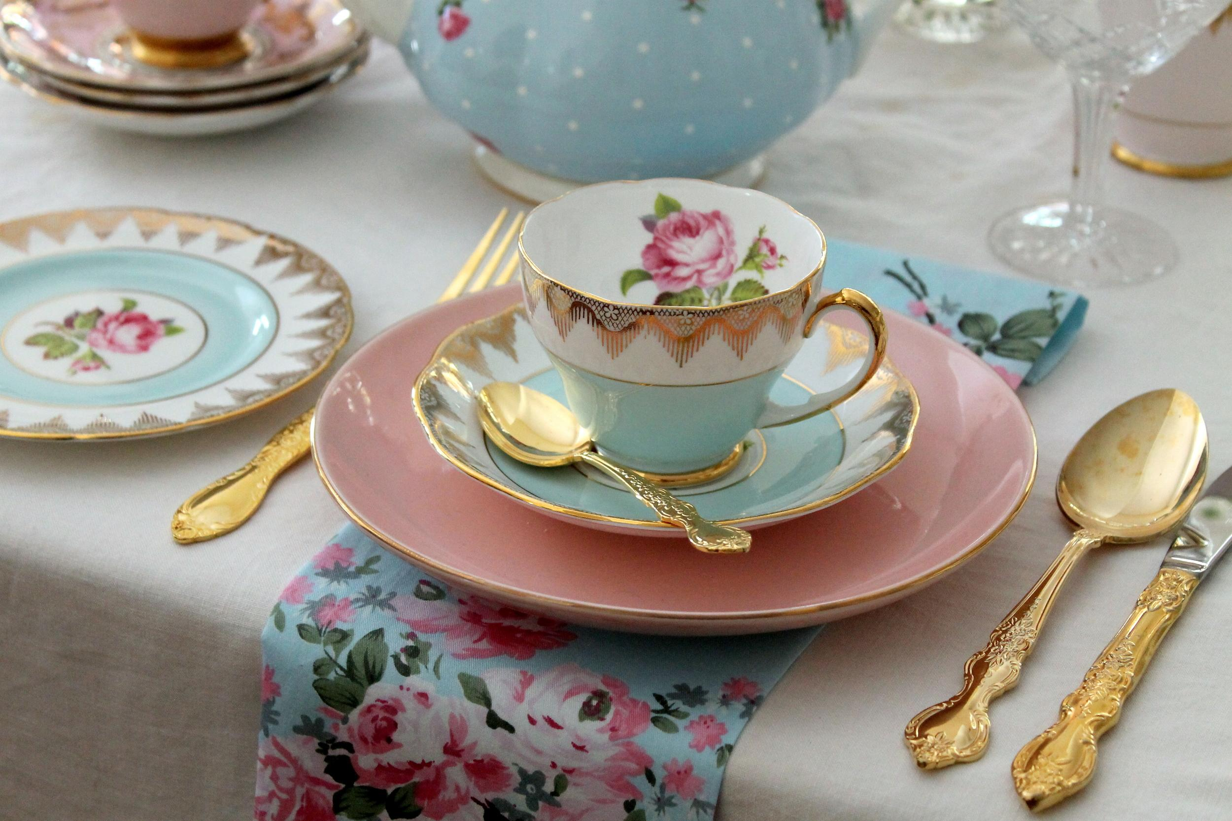 High tea bridal shower place setting pink and blue vintage teacups plates gold cutlery flatware on lace tablecloth - wedding party
