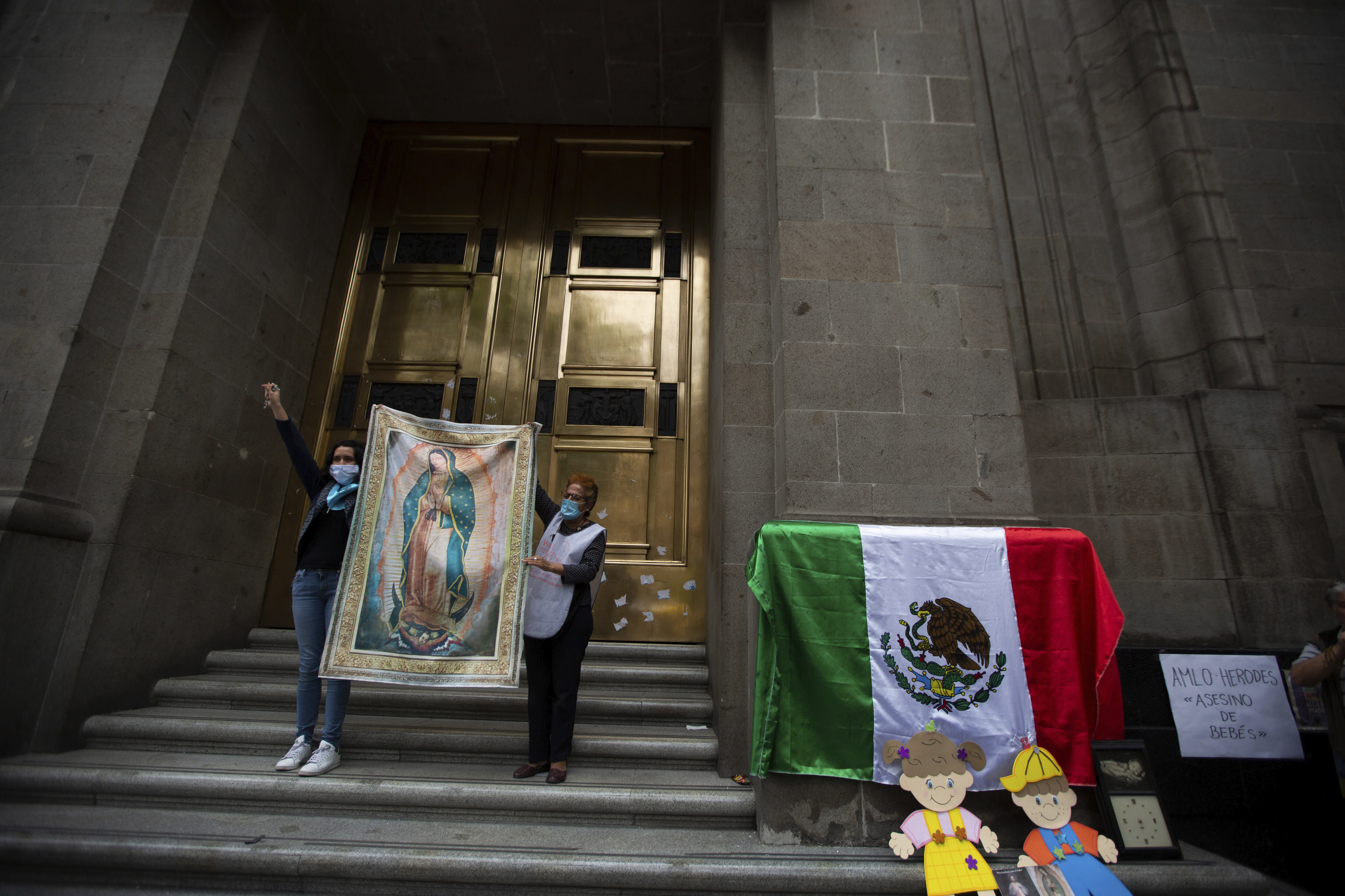 Activists against abortion hold up an image of Our Lady of Guadalupe at the entrance of the Supreme Court to celebrate the court's decision against an injunction in Veracruz state that aimed to decriminalize abortion for all cases within the first 12 weeks of pregnancy in Mexico City, Wednesday, July 29, 2020. Two of Mexico's 32 states have decriminalized abortion. (AP Photo/Fernando Llano)