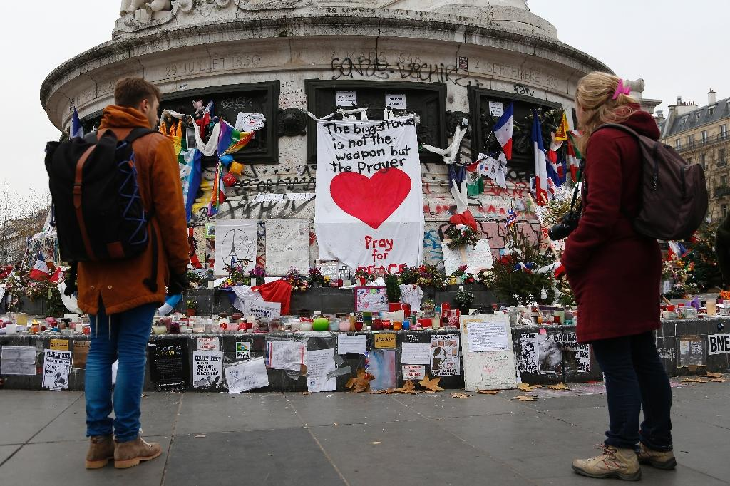 People gather in front of a makeshift memorial in Place de la Republique square in Paris on December 13, 2015