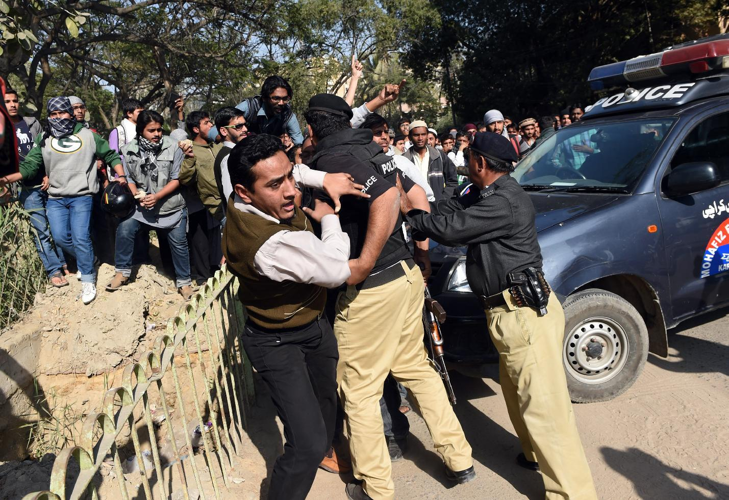 Police try to stop activists of the Jamaat-e-Islami religious party during a protest against the printing of satirical sketches of the Prophet Muhammad by French magazine Charlie Hebdo, near the French consulate in Karachi, on January 16, 2015 (AFP Photo/Asif Hassan)