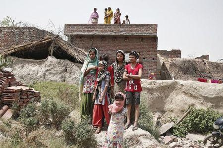 Villagers stand as they watch the house of one of the two teenage girls, who were raped and hanged from tree at Budaun