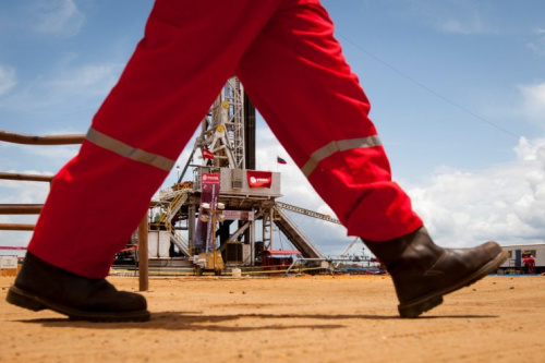 An oil worker walks past a drilling rig at an oil well operated by Venezuela's state oil company PDVSA in Morichal July 28, 2011. (Reuters)