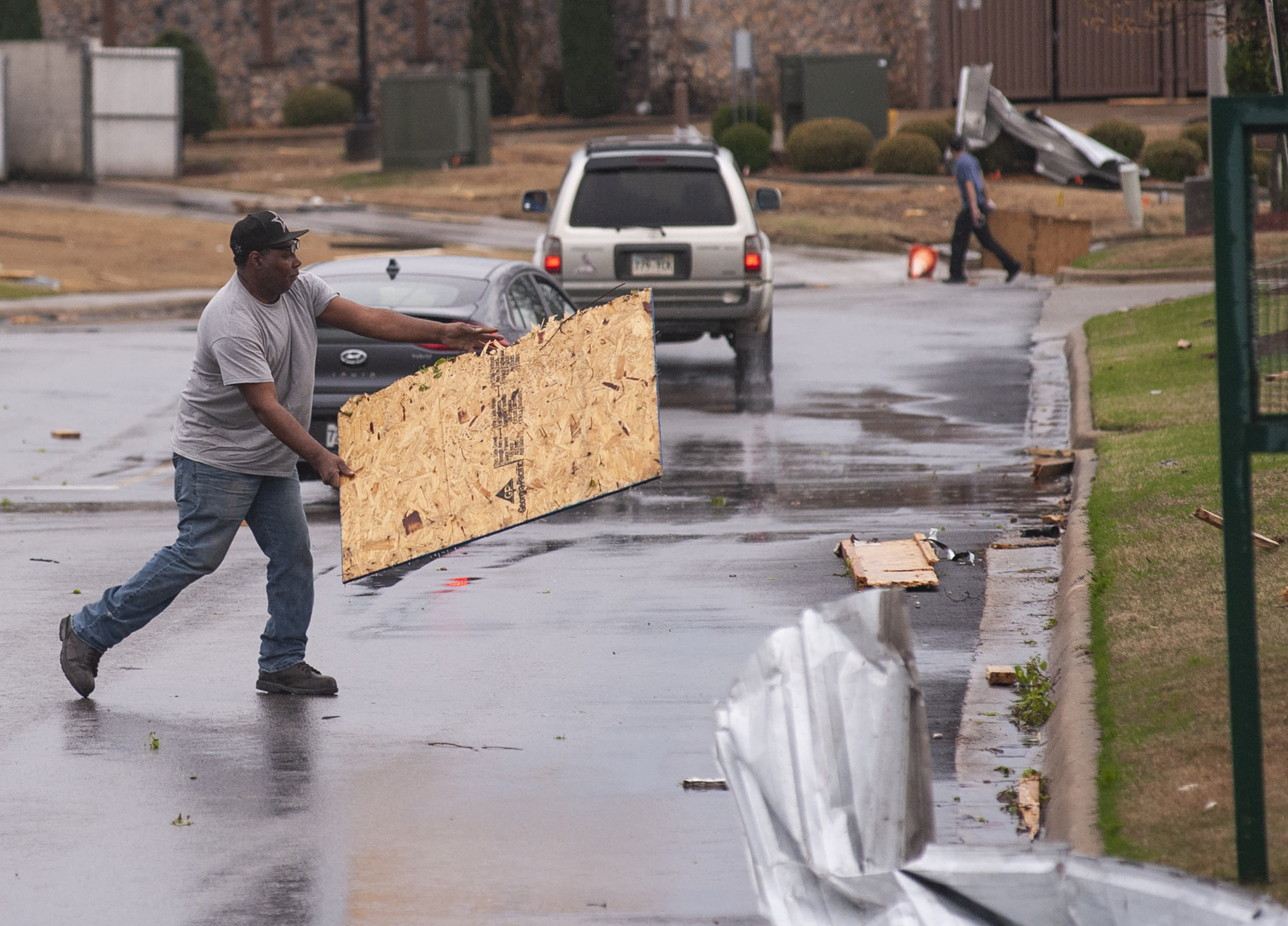 Darrell Britt gets out of his vehicle to move debris as motorists are directed to drive through the parking lot at The Mall at Turtle Creek after a tornado touched down Saturday, March 28, 2020, in Jonesboro, Ark. (Quentin Winstine/The Jonesboro Sun via AP)
