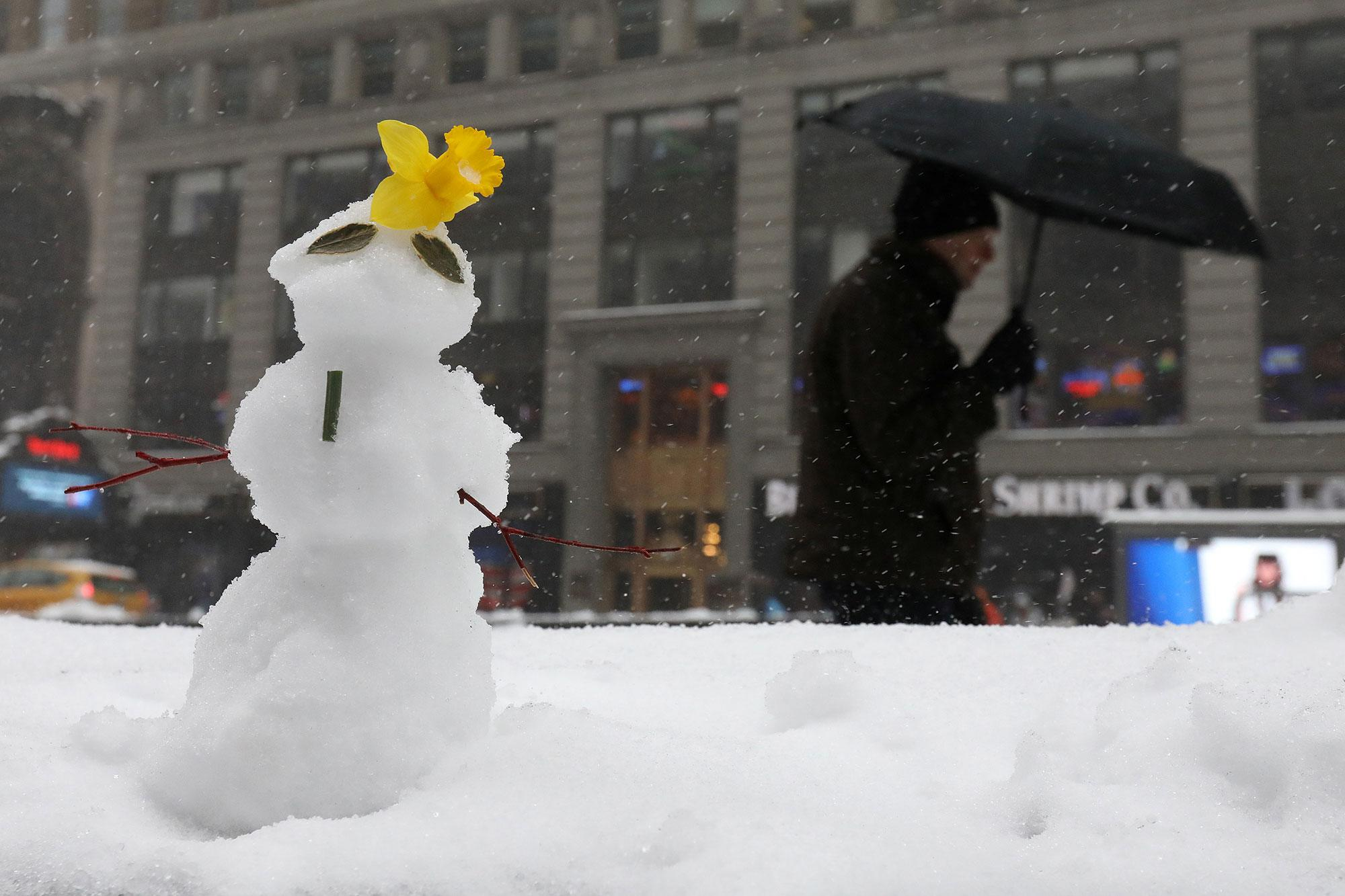 <p>A man walks with an umbrella past a snowman during a snow storm in Times Square in the Manhattan borough of New York, New York, U.S. March 14, 2017. (Carlo Allegri/Reuters) </p>