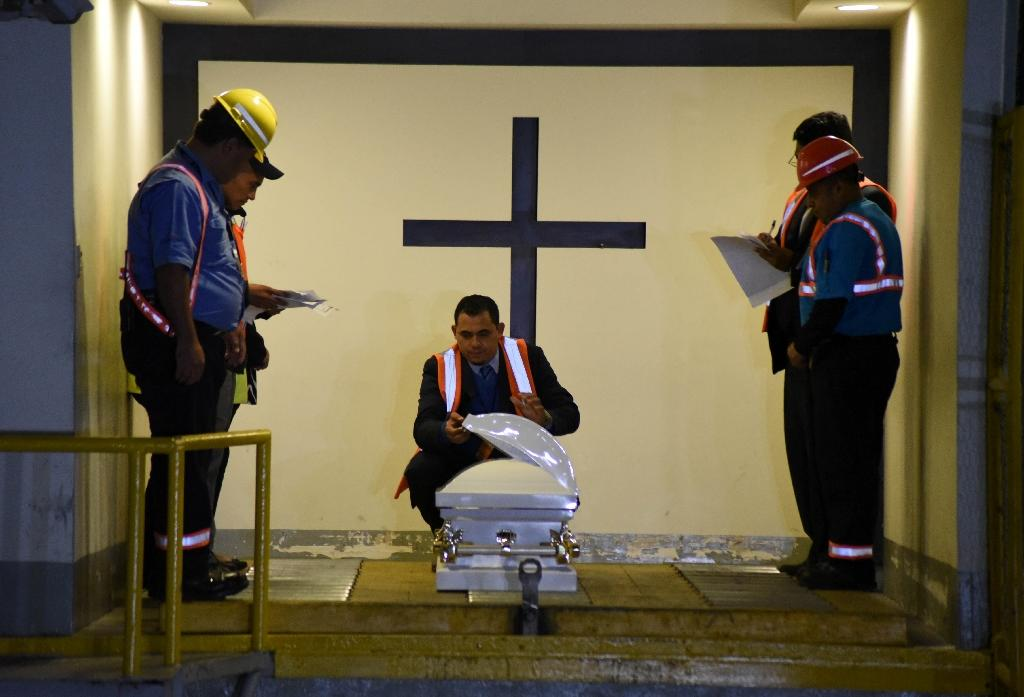 Funeral home employees in Guatemala prepare the coffin holding the repatriated body of eight-year-old migrant Felipe Gomez