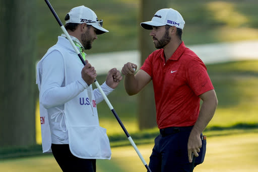 Matthew Wolff, right, bumps fists with his caddie after finishing the third round of the US Open Golf Championship, Saturday, Sept. 19, 2020, in Mamaroneck, N.Y. (AP Photo/Charles Krupa)