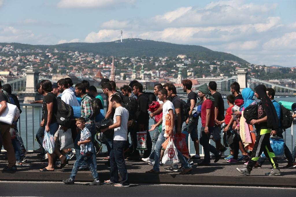 Hundreds of migrants walk after leaving the transit zone of the Budapest train station, on September 4, 2015