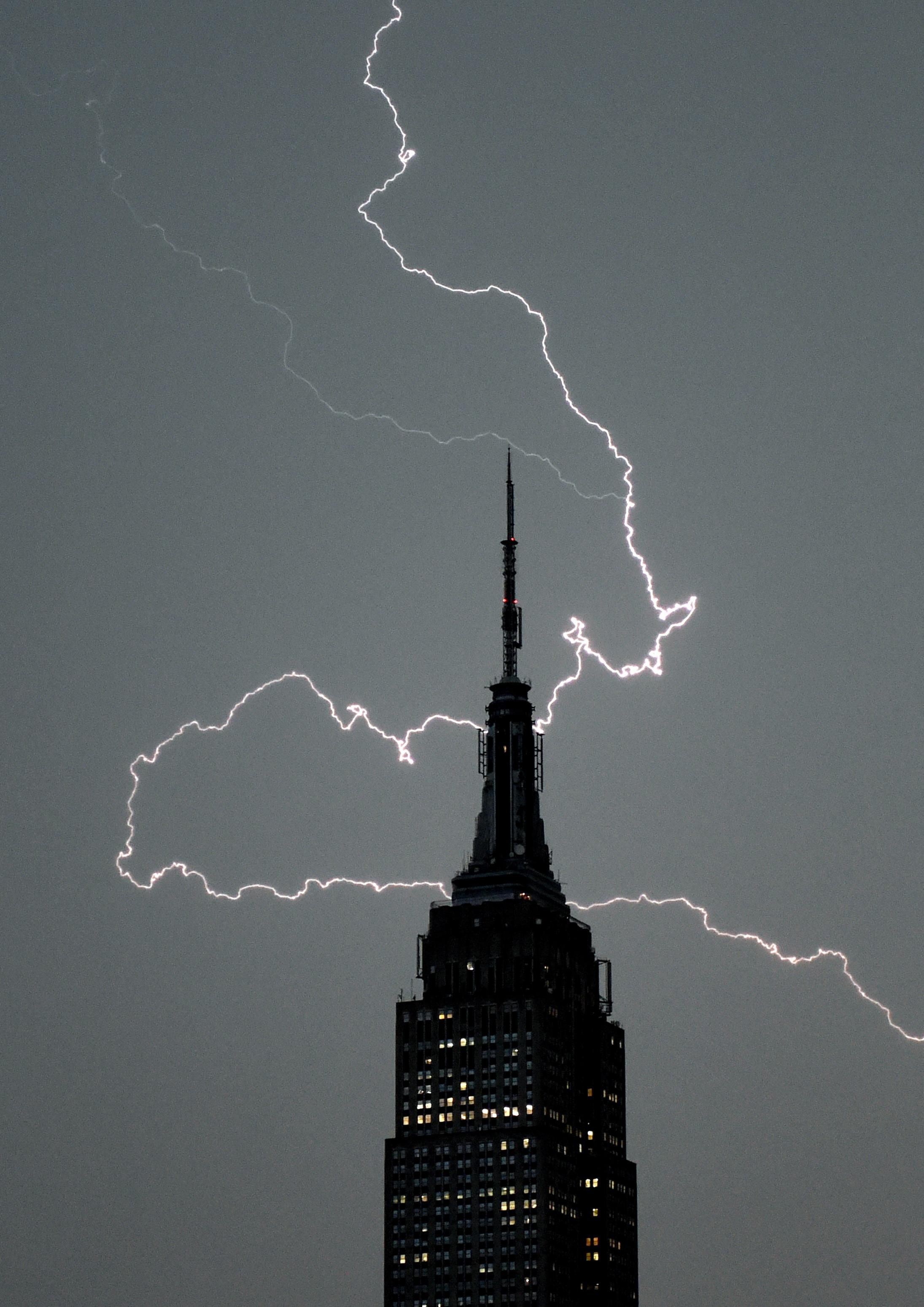 Lighting strikes over the Empire State Building as a major storm moves through New York City on July 2, 2014 (AFP Photo/Timothy A. Clary)