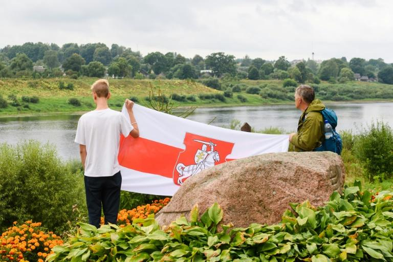 Two men hold Belarussian opposition flag near the river during a solidarity campaign for Belarussians along the border with Belarus in Piedruja, Latvia.