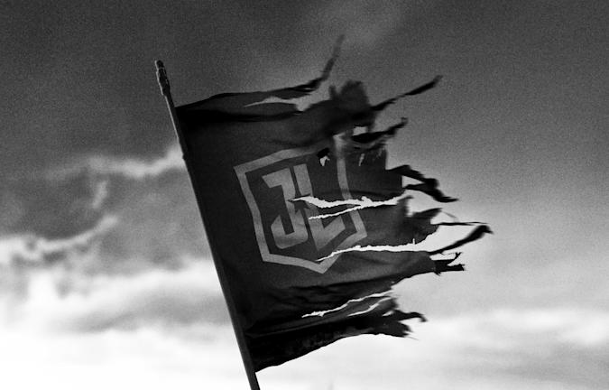 A black and white image showing a torn and tattered Justice League flag flying against a foreboding cloudy sky.
