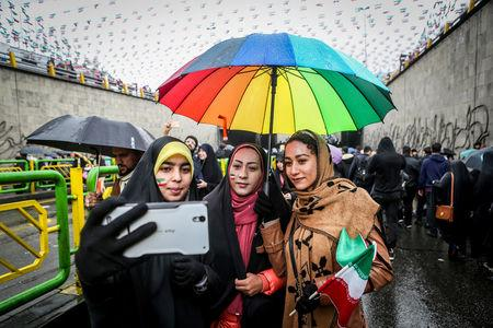 FILE PHOTO: An Iranian woman take selfies during a ceremony to mark the 40th anniversary of the Islamic Revolution in Tehran, Iran February 11, 2019. Vahid Ahmadi/Tasnim News Agency/via REUTERS