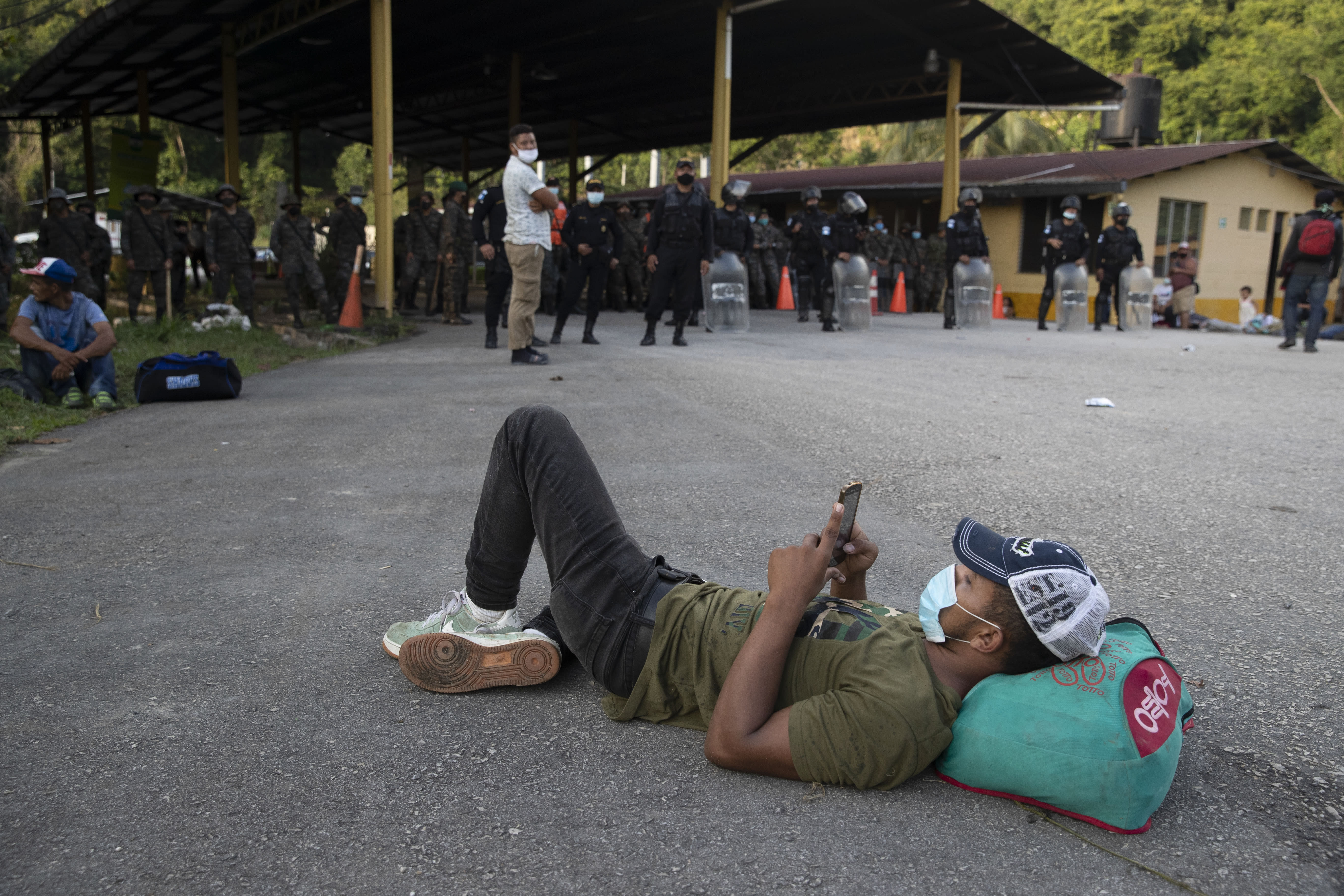 An Honduran migrant rests in front of a road block set by security forces in Poptun, Guatemala, Friday, Oct. 2, 2020. Guatemala vowed to detain and return members of a caravan of hundreds of migrants that set out from neighboring Honduras in hopes of reaching the United States, saying they represent a health threat amid the coronavirus pandemic. (AP Photo/Moises Castillo)