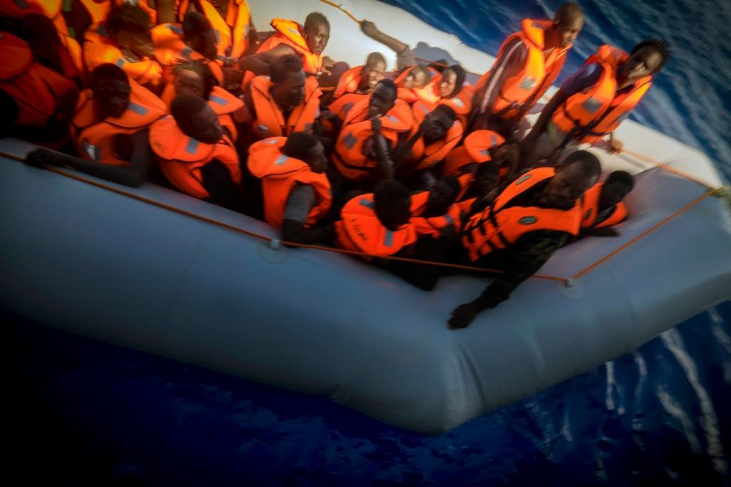 A member of MSF carries a young migrant aboard a zodiac during a rescue operation off the coast of Libya on September 28, 2015