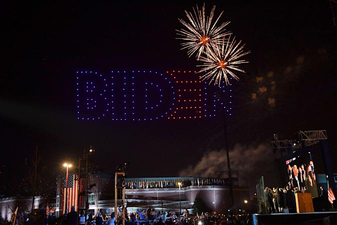 Fireworks are launched as illuminated drones spell BIDEN in the sky as US President-elect Joe Biden with his wife doctor Jill Biden alongside Vice President-elect Kamala Harris and her husband Douglas Emhoff and their families watch in Wilmington, Delaware, on November 7, 2020, after being declared the winners of the presidential election. - Democrat Joe Biden was declared winner of the US presidency November 7, defeating Donald Trump and ending an era that convulsed American politics, shocked the world and left the United States more divided than at any time in decades. (Photo by ANGELA  WEISS / AFP) (Photo by ANGELA  WEISS/AFP via Getty Images)