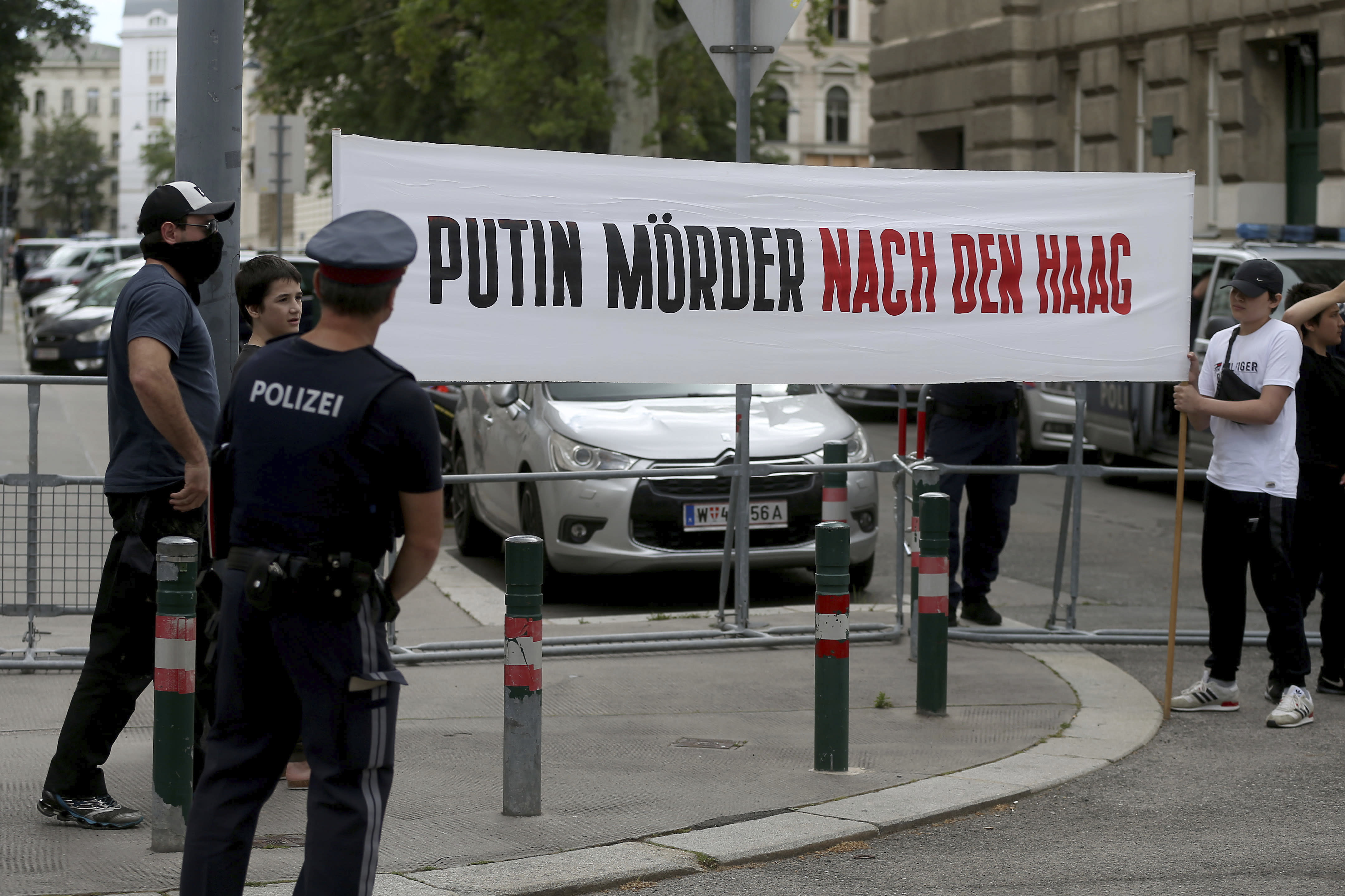 """Chechen protesters hold a banner that reads: """"Putin murderer to The Hague"""" outside of the Russian embassy in Vienna, Austria, Tuesday, July 7, 2020. A 43-year-old ethnic Chechen who had lived in Austria for more than a decade was killed over the weekend. (AP Photo/Ronald Zak)"""