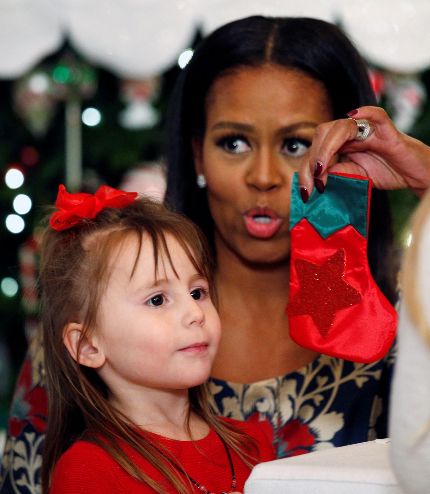 <p>First lady Michelle Obama holds up a holiday craft for a child during an event welcoming military families to the White House to view the holiday decorations in Washington on Nov. 29, 2016. (Photo: Kevin Lamarque/Reuters) </p>