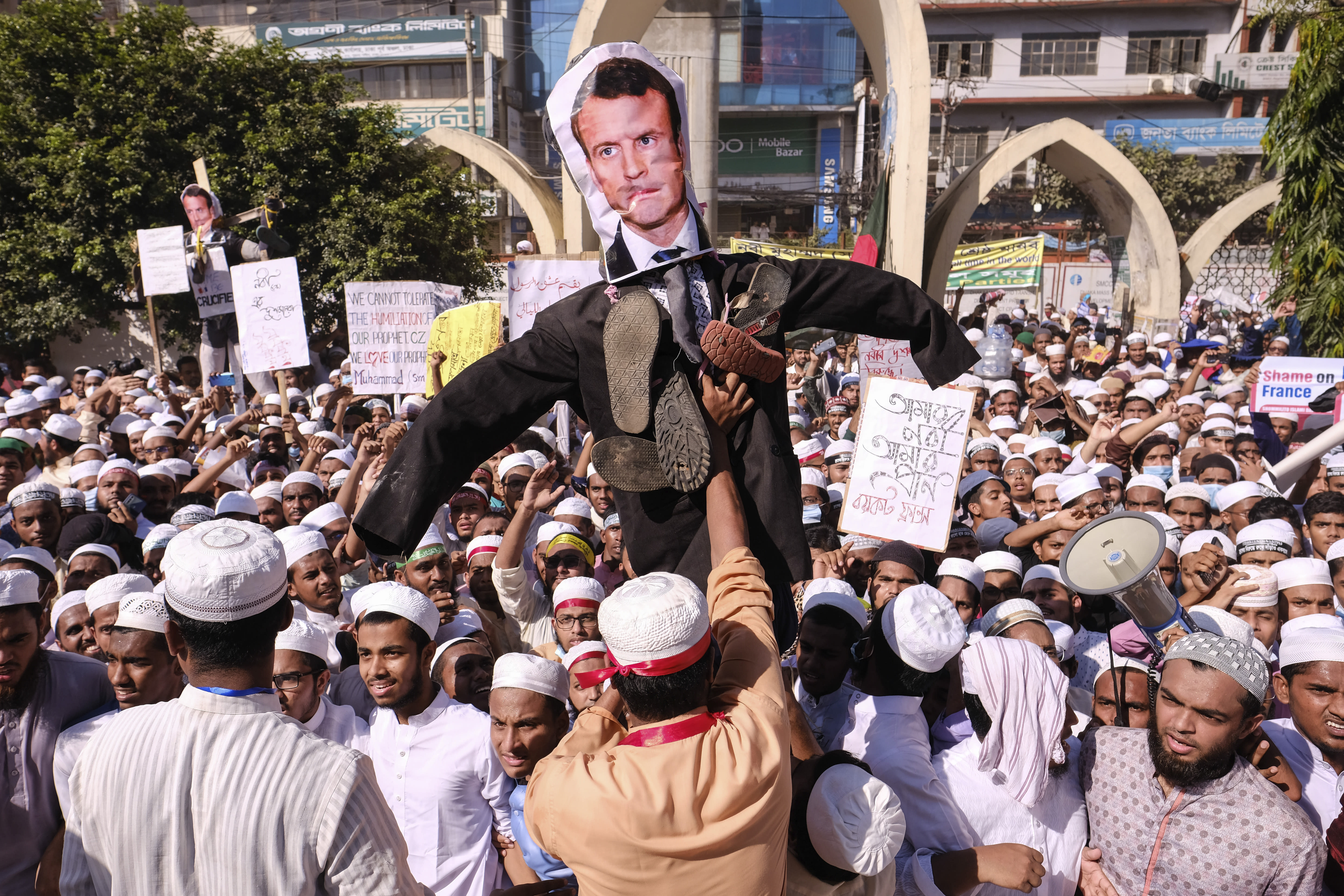 Supporters of Islamist parties carry an effigy of French President Emmanuel Macron during a protest after Friday prayers in Dhaka, Bangladesh, Friday, Oct. 30, 2020. Thousands of Muslims and activists marched through streets and rallied across Bangladesh's capital on Friday against the French president's support of secular laws that deem caricatures of the Prophet Muhammad as protected under freedom of speech. (AP Photo/Mahmud Hossain Opu)