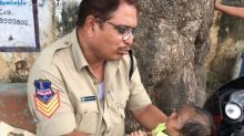 Police officer in India adorably watches baby so mom can take exam