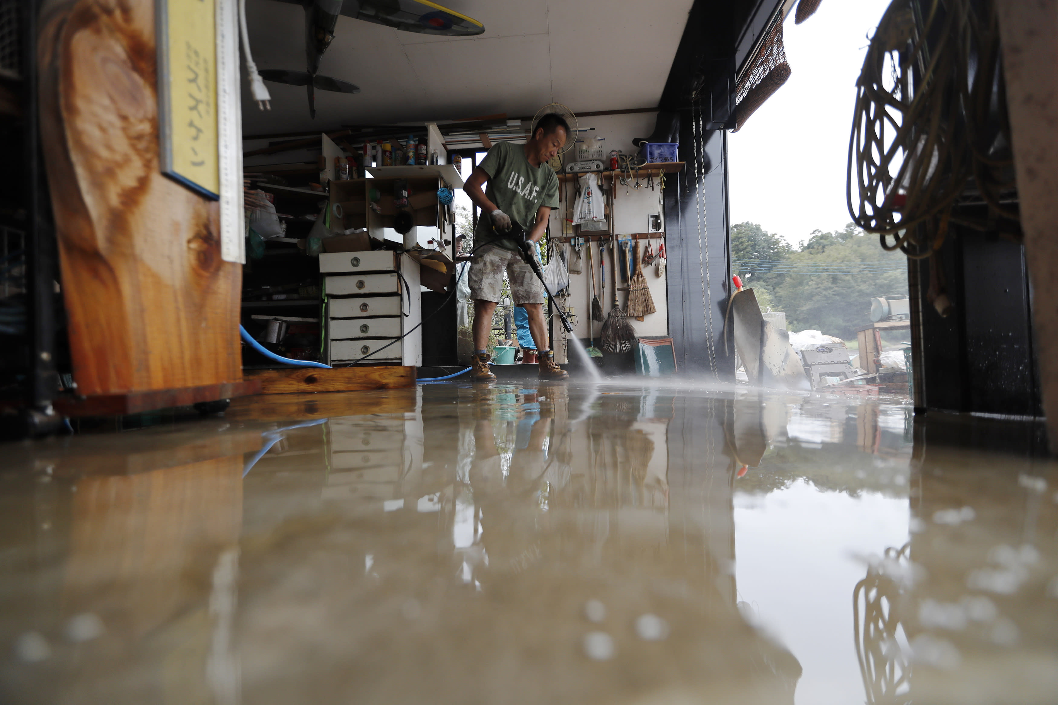 A volunteer helps clean up Monday, Oct. 14, 2019, in Kawagoe City, Japan. Typhoon Hagibis dropped record amounts of rain for a period in some spots, according to meteorological officials, causing more than 20 rivers to overflow. Some of the muddy waters in streets, fields and residential areas have subsided. But many places remained flooded, with homes and surrounding roads covered in mud and littered with broken wooden pieces and debris. (AP Photo/Eugene Hoshiko)