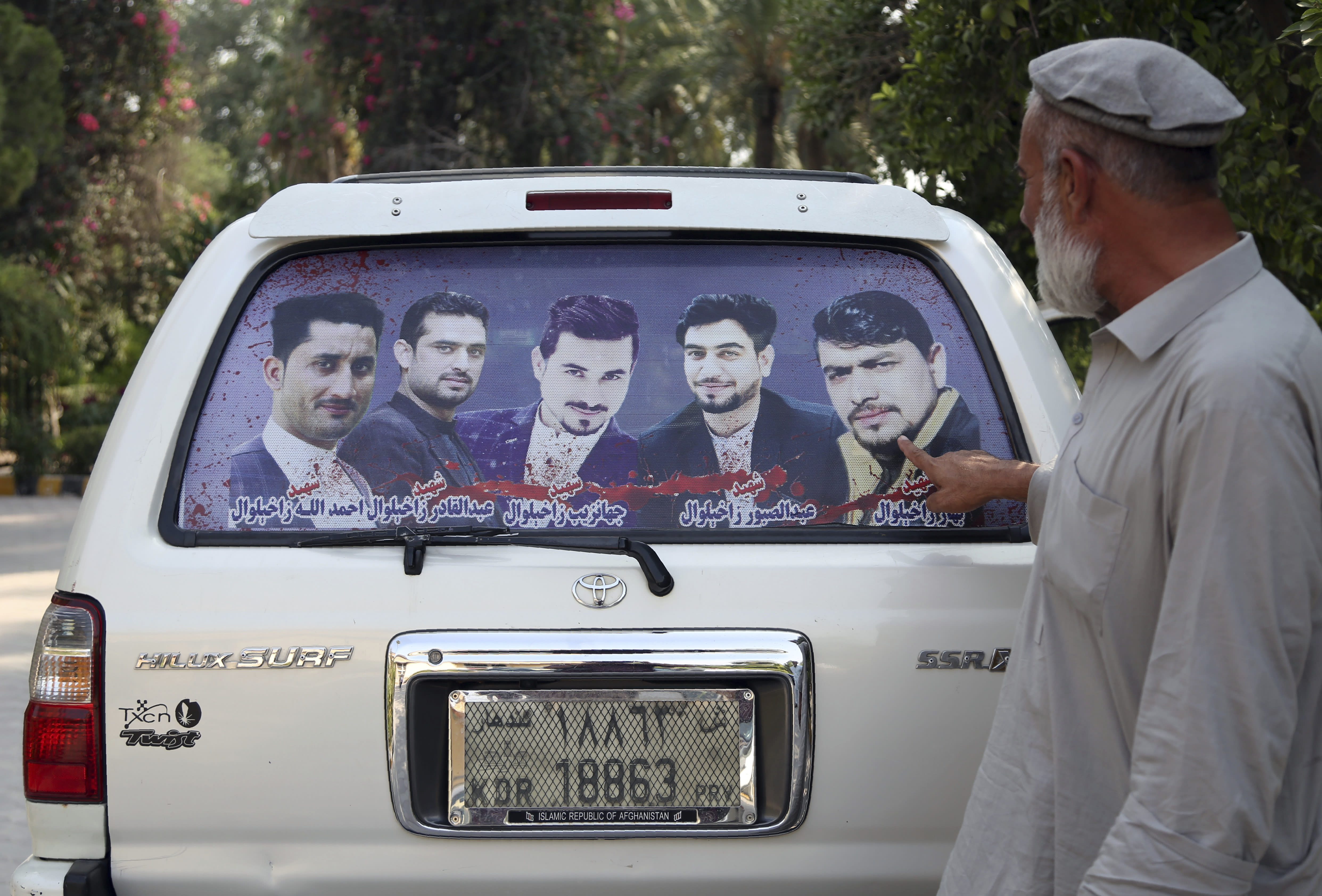 In this Tuesday, Oct. 1, 2019, photo, Zakhiwal's uncle, Mohammad Yaqoob Malikzada shows pictures of four brothers in the back of his car, who ware killed during a raid by the Afghan soldiers trained by CIA only known as Unit 02 after an interview to the Associated Press in Jalalabad city east of Kabul, Afghanistan, Anger is mounting over the increasing numbers of civilians dying in misdirected US aerial strikes and heavy- handed tactics of CIA-trained Afghan force. Some Afghans calling for Americans to be tried in Afghan courts. (AP Photo/Rahmat Gul)