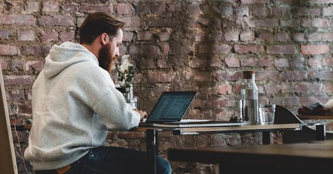 Stock image of a man using a laptop at what appears to be a coffee shop.