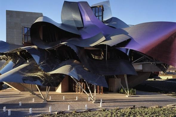 """<p> Deep wine-growing history meets 21st century avant-garde design at Hotel Marques de Riscal in Elciego, Spain. In case you hadn't guessed already, this striking hotel was designed by renowned architect Frank Gehry to embrace the past with the surrounding villages that provide a medieval setting and the future with the dazzling foil-like exterior. Hotel Marques de Riscal is nestled in the stunning Vinos de los Herederos del Marques de Riscal's vineyard with the hotel's spectacular curves, titanium roof and asymmetric walls providing a magnificent contrast to the historic wine cellars designed in 1858. Inside there are 43 uniquely luxurious rooms and suites that are 'thrown' in two buildings connected by a suspended footbridge, a fabulous wine bar (of course!) and the Vinotherapie Spa Caudalie to keep with the vineyard theme. Visit <a href=""""http://www.starwoodhotels.com/luxury/property/overview/index.html?propertyID=1539"""" target=""""_blank"""">starwoodhotels.com</a></p>"""