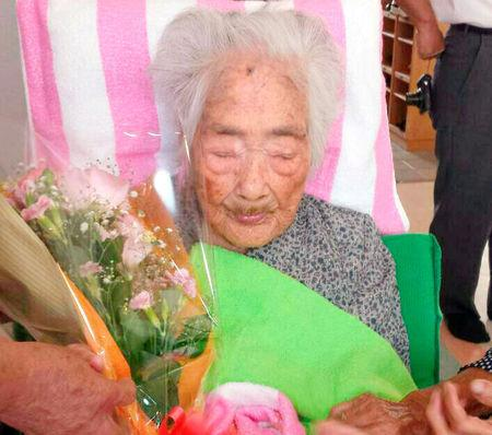 Nabi Tajima, born in 1900, holds a bouquet in Japanese southwestern island of Kikaijima
