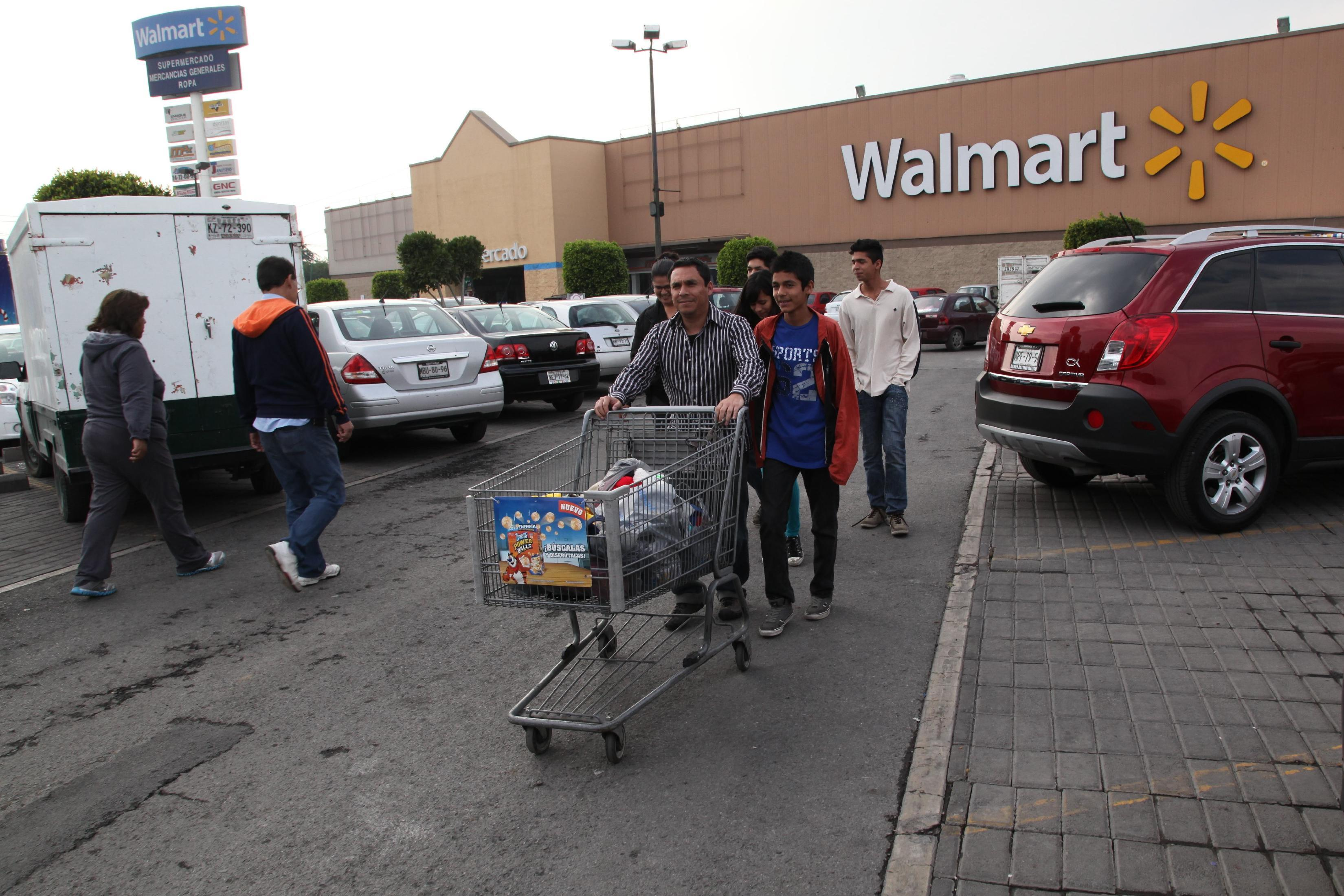 In this Thursday, Dec. 26, 2013 photo, a family leaves a local Walmart in Mexico City. Looking around a Mexico dotted by Starbucks, Wal-Marts and Krispy Kreme outlets, it's hard to remember the country before the North American Free Trade Agreement, which has dramatically expanded consumer choice and trade since it took effect 20 years ago.(AP Photo/Marco Ugarte)