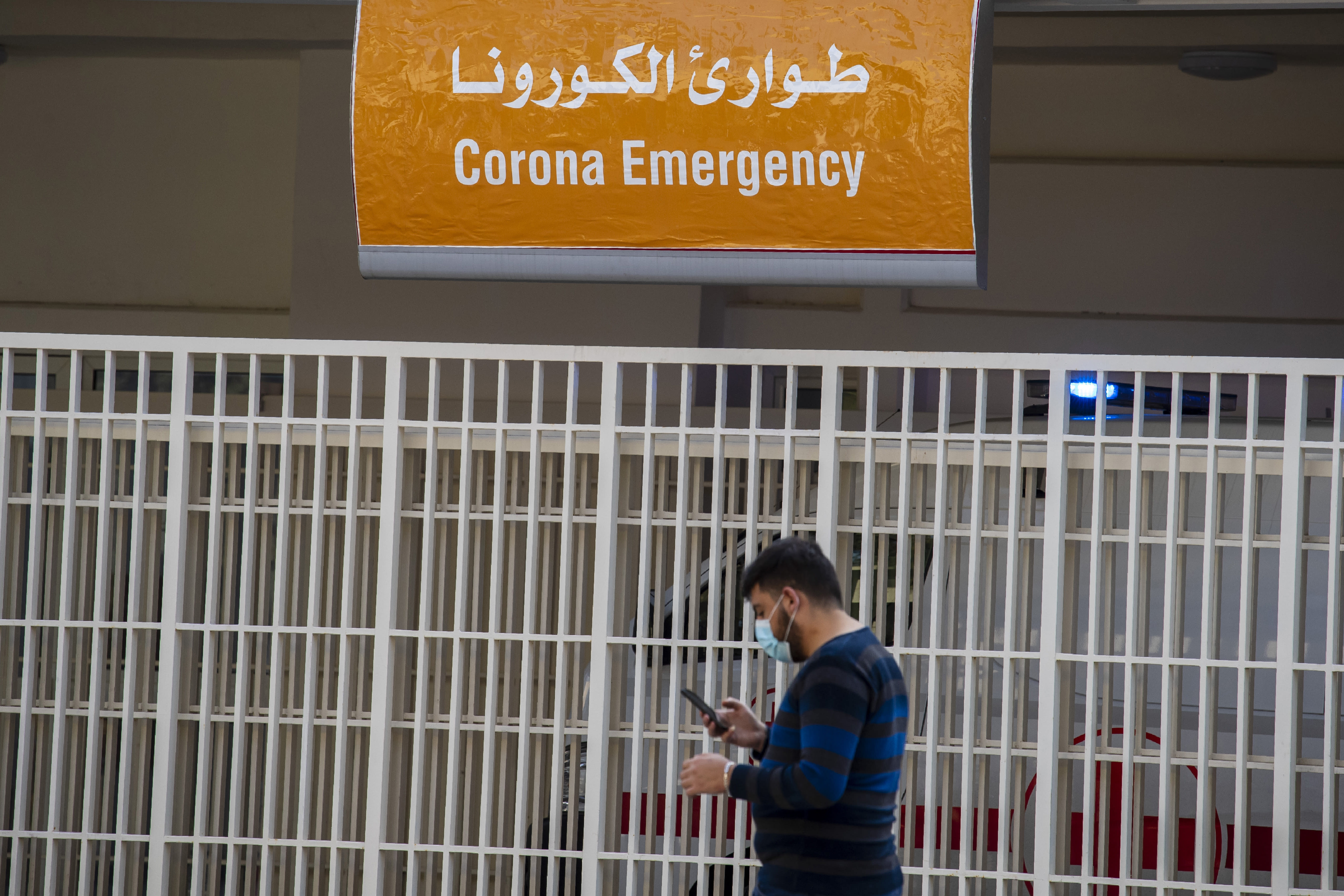 A man wears a mask as he checks his mobile phone while passing the emergency entrance of the government-run Rafik Hariri University Hospital where most of the Lebanese coronavirus cases are treated in Beirut, Lebanon, Thursday, March 26, 2020. The new coronavirus causes mild or moderate symptoms for most people, but for some, especially older adults and people with existing health problems, it can cause more severe illness or death. (AP Photo/Hassan Ammar)