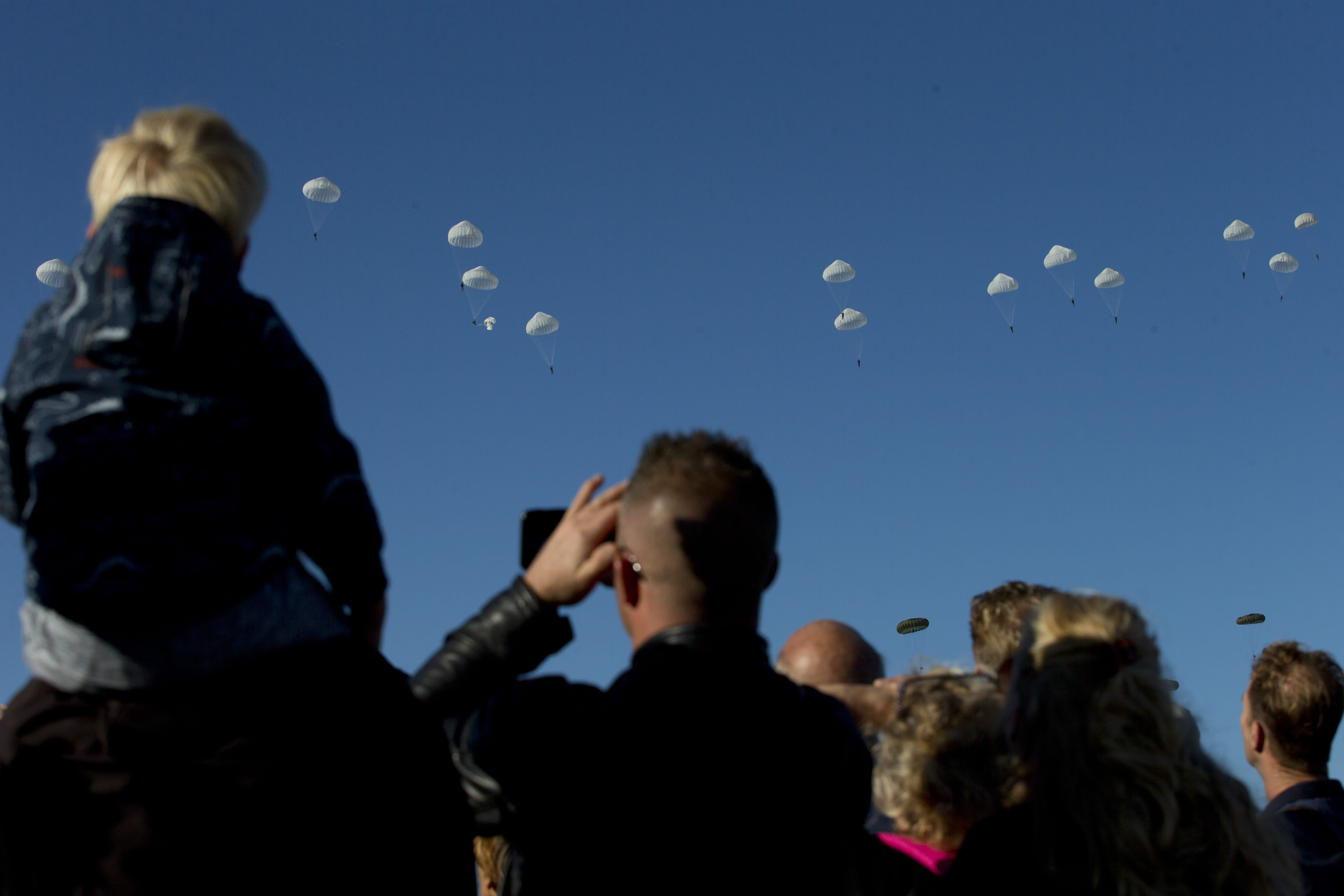 Spectators watch a mass parachute drop at Ginkel Heath, eastern Netherlands, Saturday, Sept. 21, 2019, as part of commemorations marking the 75th anniversary of Operation Market Garden, an ultimately unsuccessful airborne and land offensive that Allied leaders hoped would bring a swift end to World War II by capturing key Dutch bridges and opening a path to Berlin. (AP Photo/Peter Dejong)
