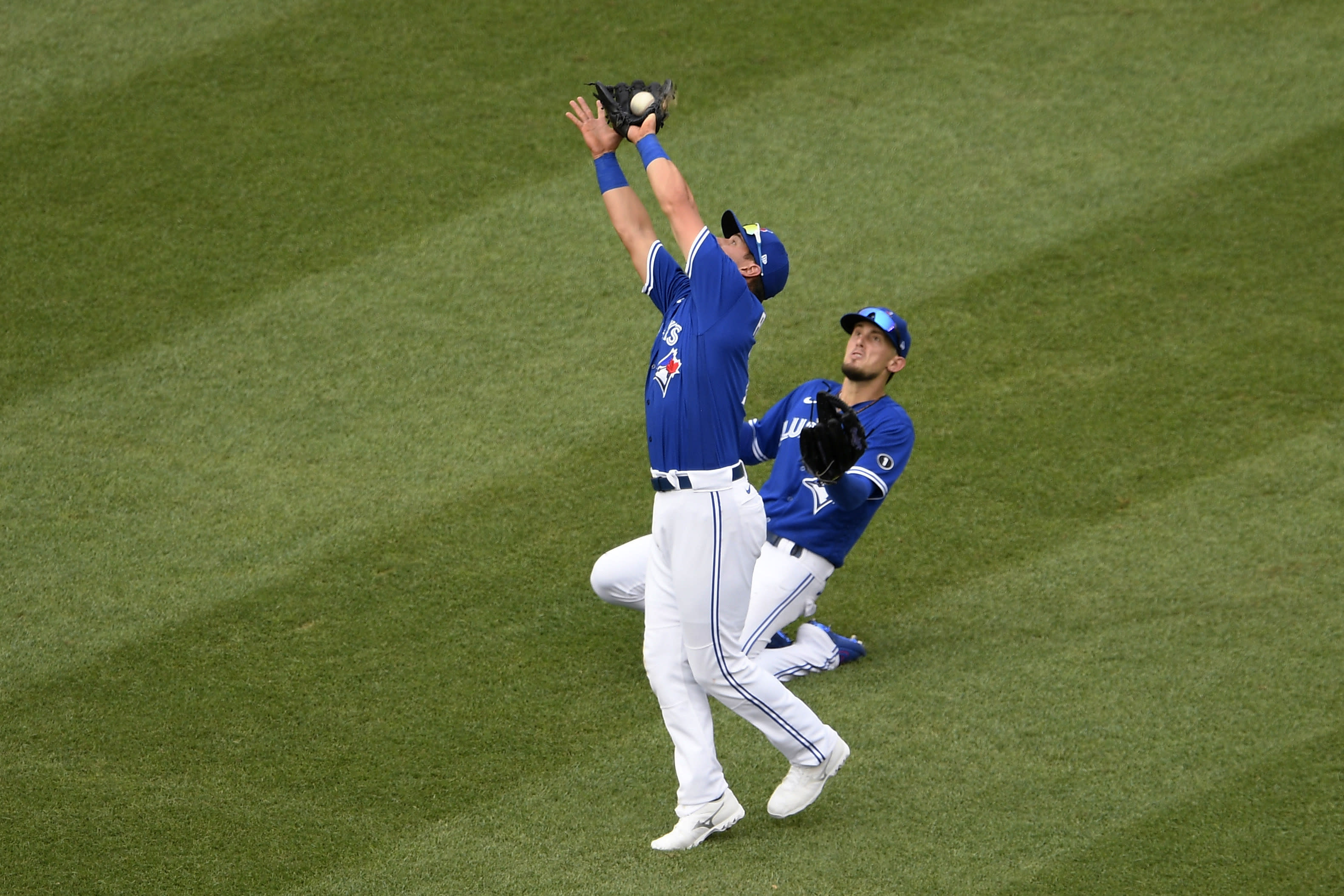 Toronto Blue Jays second baseman Joe Panik, front, makes a catch for the out on a fly ball by Washington Nationals' Adam Eaton during the fourth inning of a baseball game Thursday, July 30, 2020, in Washington. At right is Blue Jays' Cavan Biggio. (AP Photo/Nick Wass)