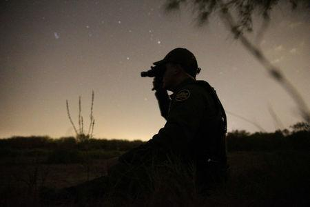 A border patrol agent uses night vision goggles to look for immigrants who illegally crossed the border from Mexico into the U.S. in the Rio Grande Valley sector, near McAllen, Texas, U.S., April 2, 2018. REUTERS/Loren Elliott