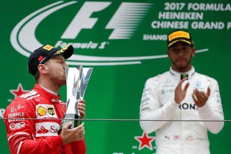 Piloto da Ferrati, Sebastian Vettel, beija taça no pódio do GP da China de F1