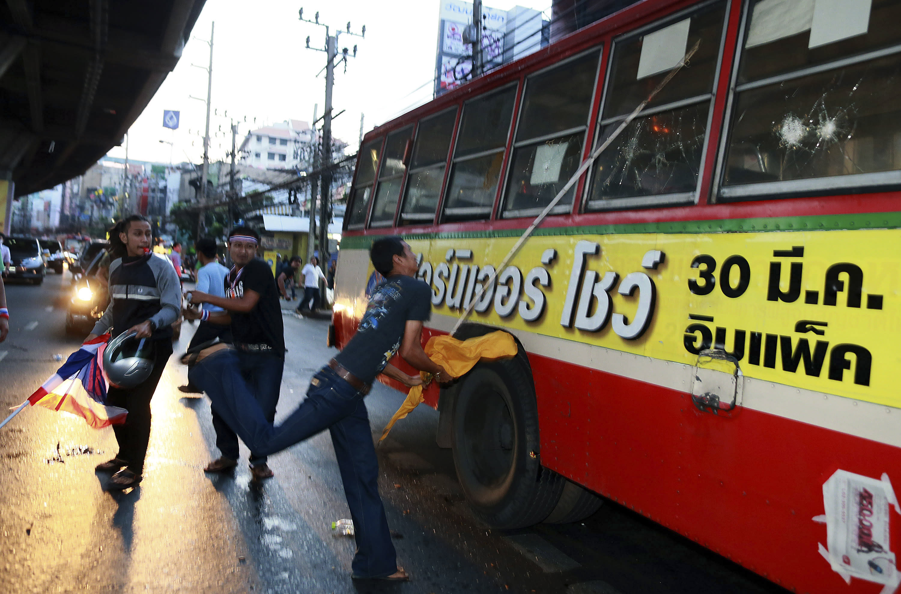 Anti-government protesters attack people they suspected of supporting the current Thai government on the bus in Bangkok,Thailand Saturday, Nov. 30, 2013. A mob of anti-government protesters smashed the windows of a moving Bangkok bus Saturday in the first eruption of violence after a week of tense street protests.(AP Photo/Wason Wanichakorn)